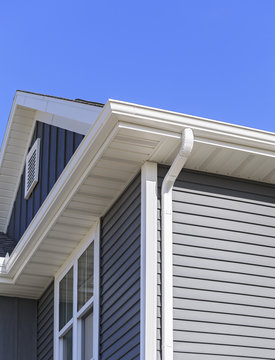 Grey siding, gutters, and soffit on a new home