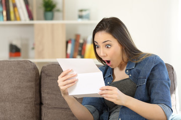 Amazed woman reading surprising news in a letter
