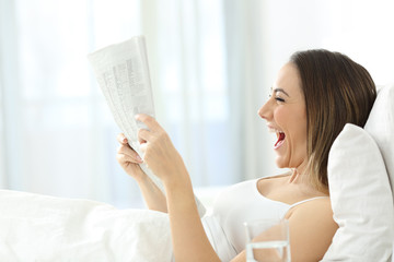 Excited woman reading a newspaper on the bed