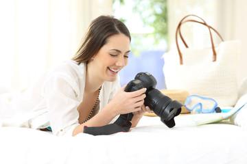 Tourist checking camera photos at hotel room