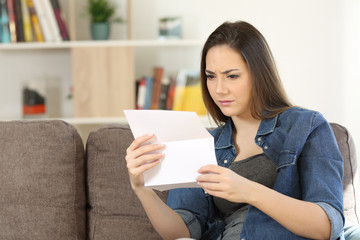 Worried woman reading a letter at home