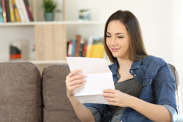 Satisfied woman reading a letter at home