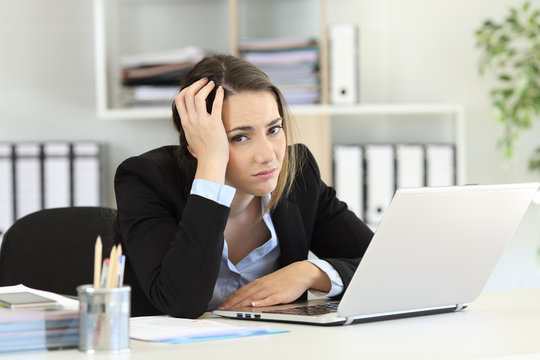 Worried office worker looking at camera