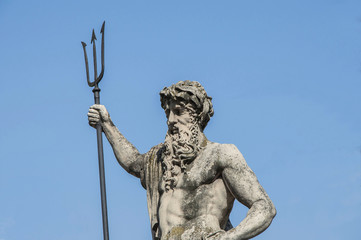The ancient statue of the god of the seas and oceans Neptune (Poseidon). Famous tourist attraction  against a blue sky in summer