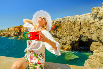 Woman takes photo of Boca do Inferno, a cliff formation, Cascais, Atlantic Ocean, Portugal.Female tourist takes pictures by mobile phone with Portugal flag of Hell's Mouth a touristic sightseeing spot