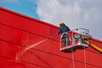 Worker wearing safety harness washes wall facade at height on modern building in a crane.