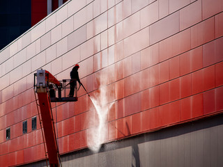 Worker wearing safety harness washes wall facade at height on modern building in a crane. Fototapete