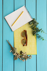 Top view close up of modern spectacles and opened copybook with pen situating on bright paper