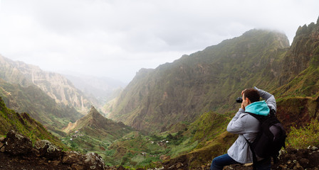 Traveler on the mountain edge making a photo of landscape. Deep clouds above green Xo-Xo Valley. Santo Antao Island, Cape Verde