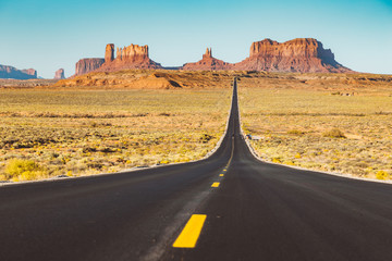 Wall Mural - Classic highway scene in Monument Valley at sunset, USA