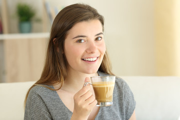Happy teen holding a coffee with milk looking at you