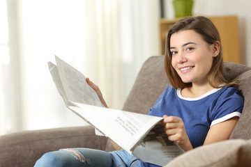 Teen reading a newspaper looking at camera at home