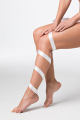 Women's legs with white ribbon