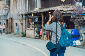 Backside of Asian traveler taking the photo in mae kam pong village, chiang mai, thailand, travel and lifestyle concept