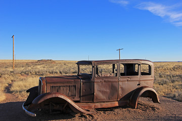 Old rusted vintage car along Route 66, near north entrance of Petrified Forest National Park, Arizona, USA