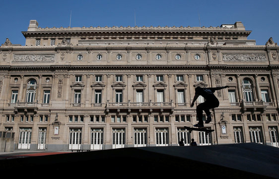 A skateboarder jumps with his skateboard in front of the Colon Theater at Buenos Aires