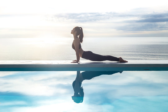 Asian young woman practice Yoga Cobra Pose on the pool above the beach in the morning,Feeling so comfortable and relax in holiday