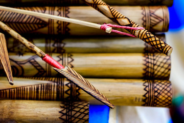 arrow showing hand made wooden bamboo carving engraved fish figure artwork on bamboo, rows of engraved bamboo sticks. tribal artwork. textured background