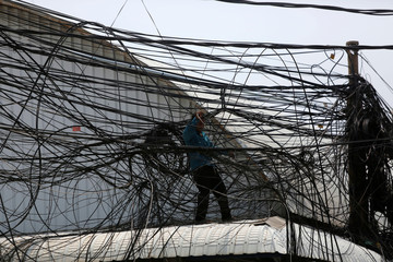 An electrician prepares electrical wires along a street in Phnom Penh