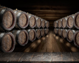 Old wooden table top and oak wine barrels at the background.
