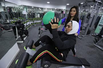 Saudi Rehab Al Mahasnha (R) works out as Rana Al Shammaai assists her at a local gym in Qatif, Saudi Arabia