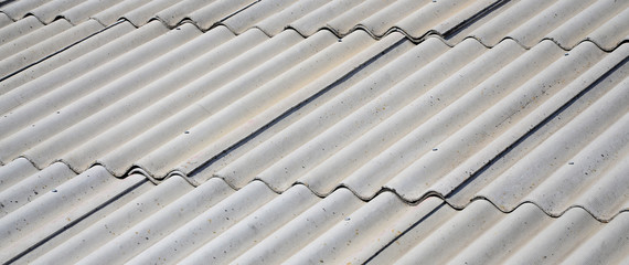 A fragment of a gray slate roof of an old sample made of asbestos material