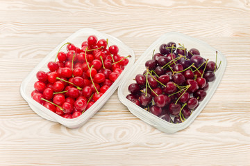 Two varieties of cherries in two different plastic containers