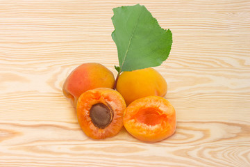 Ripe apricots and leaf on a wooden surface