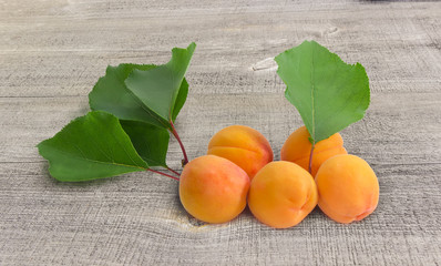 Ripe apricots with leaves on an old wooden surface