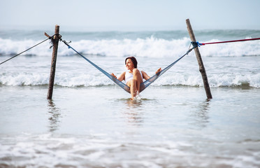 Woman in white swimsuit sits in hammock swing over the ocean waves