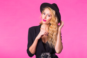 Style, people and luxury concept - Beautiful caucasian woman wearing black hat. Fashion studio portrait over pink background