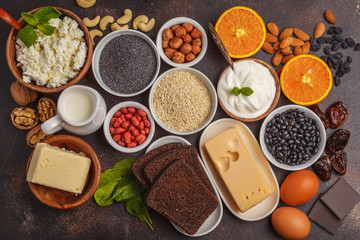 Healthy food nutrition dieting concept. Assortment of high calcium sources. Dairy products, legumes, eggs, nuts, chocolate, poppy, sesame, chocolate. Dark background, top view