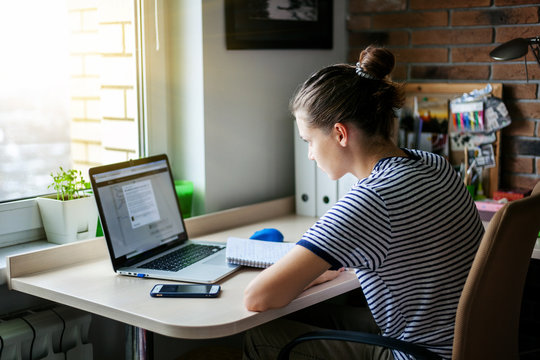Girl student freelancer working with laptop at home by the window, education and remote work, programmer, online business