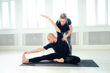 a man and a woman practicing yoga and in the studio. Morning asanas in yoga class. team work in the gym. pair yoga in a yoga class