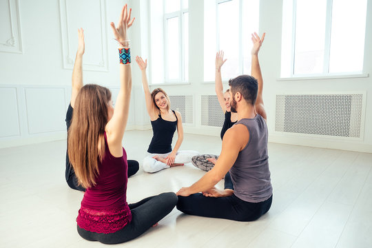 a happy group of people from men and women practicing yoga in the studio. groups of meditation , communication yoga class. the concept of group meditation and teamwork. coach and students in a circle