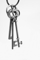 Antique keys with house wooden keyring with white background