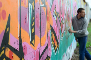 Foto op Plexiglas Paradijsvogel A young guy in a gray hoodie paints graffiti in pink and green colors on a wall in rainy weatherю Focus on the fragment of wall and blurred artist