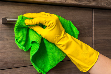 Hand in glove with green rag is cleaning stainless steel handles