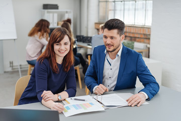 Man discussing project with woman in office