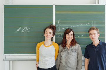 Students standing against blackboard in class