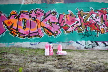 A few used paint cans lie on the ground near the wall with a beautiful graffiti painting in pink and green colors. Street art concept