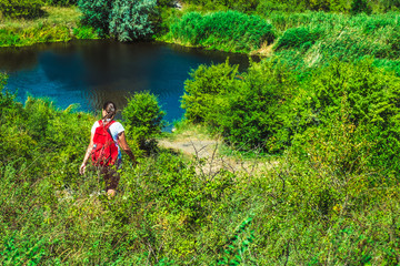 Fototapeta girl with a backpack, among the greenery on the shore of the lake