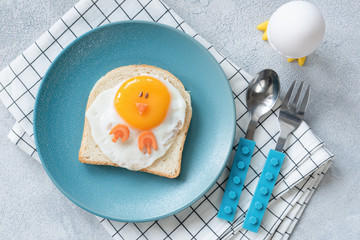 Funny egg toast for kids on blue plate, top view. Chicken shaped sandwich, food art.