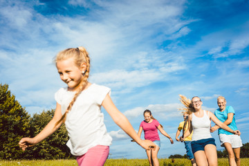 Family playing, running and doing sport in summer landscape