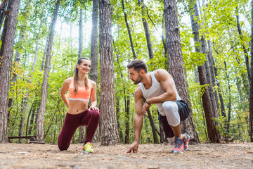 Man and woman warming up and stretching before exercise outdoors
