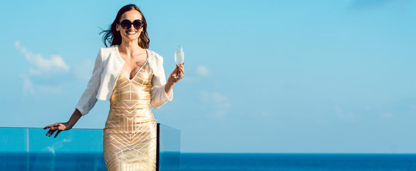 Woman drinking sparkling wine looking over ocean wearing an expensive dress