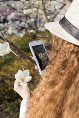 Woman taking pictures of white magnolia