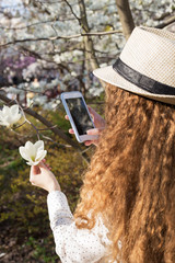 Girl taking pictures of magnolia