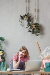 Photo of florist girl talking on phone in flower shop