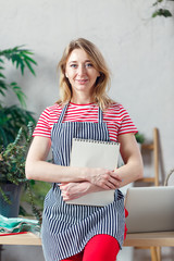 Image of smiling woman holding floral florist with blank notebook